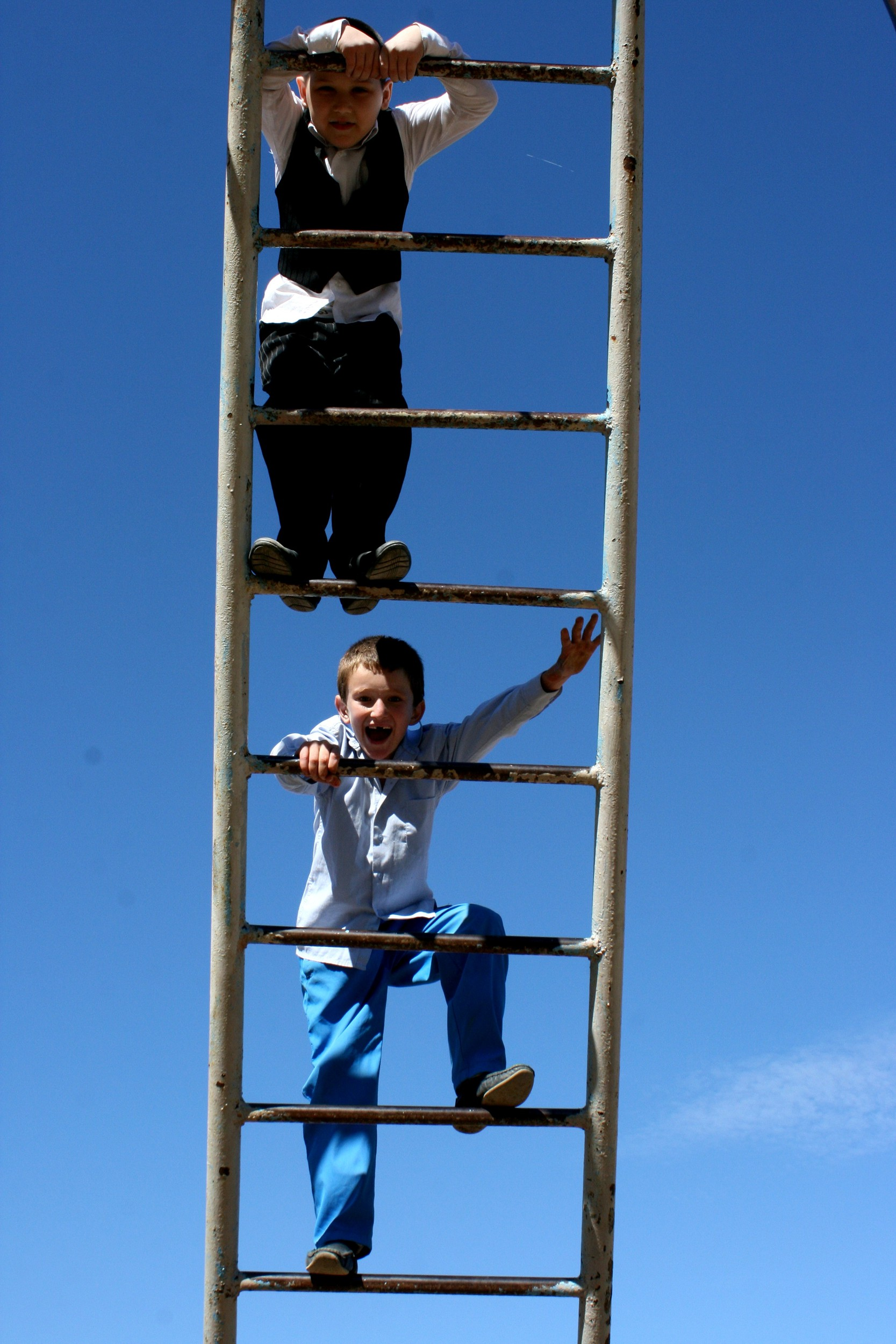 Two schoolboys climbing up the ladder on the school's playground. Astrakhan, 2nd October.