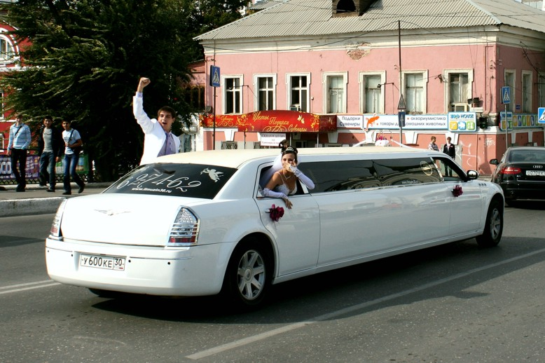 Newly married couple waving to passers-by from a wedding limousine